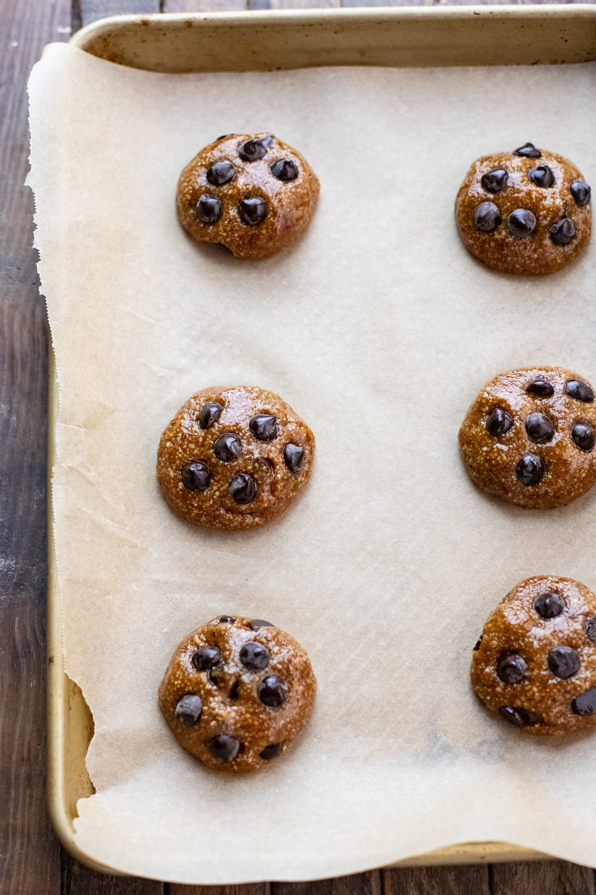chocolate chip cookie dough balls arranged on cookie sheet lined with parchment paper.