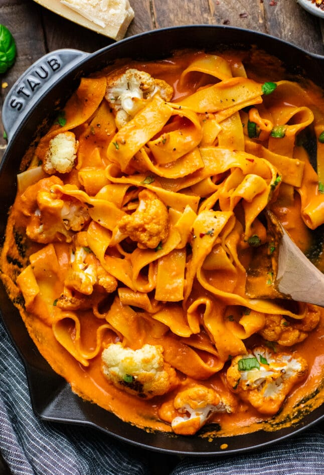 a skillet pan with orange red pepper sauce with pasta noodles, roasted cauliflower, and a wooden spoon in it.