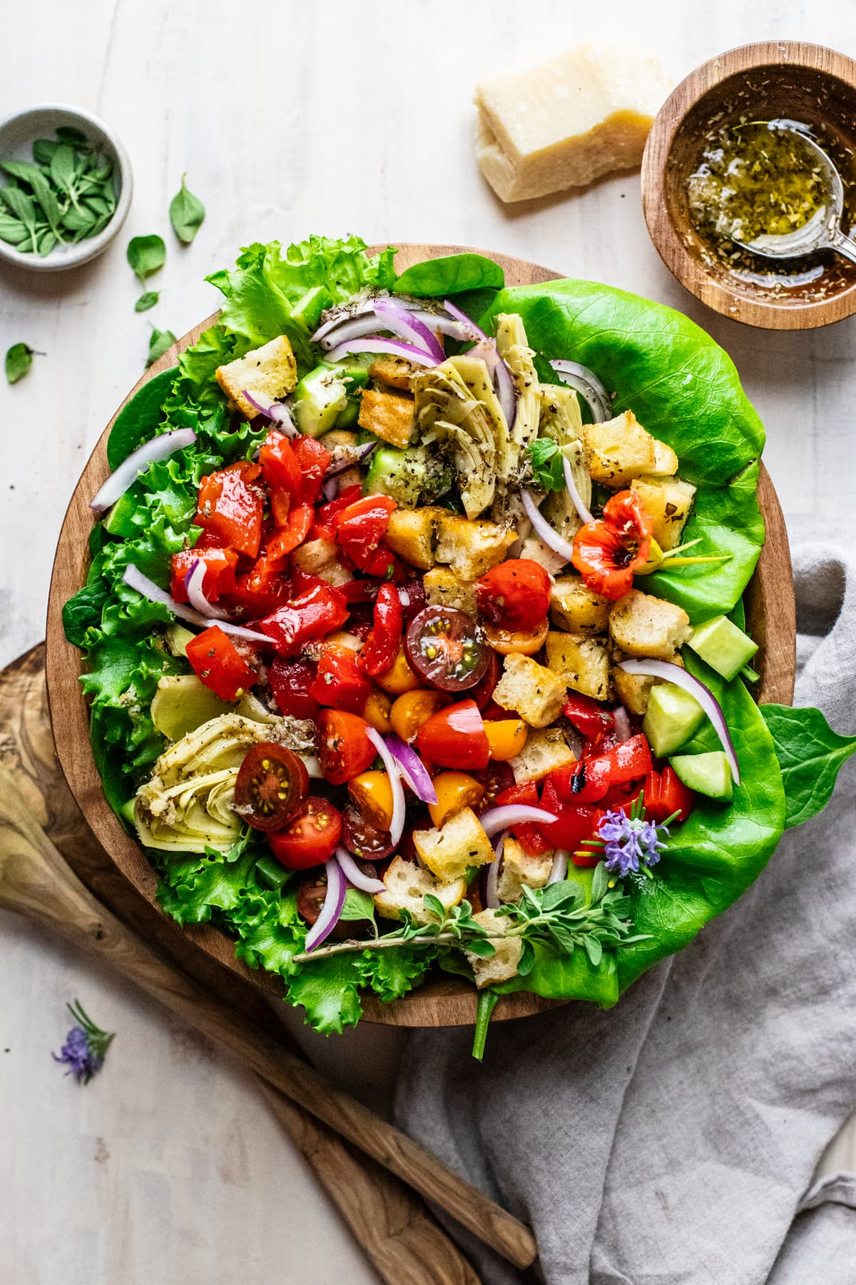wooden bowl with italian salad and greens in it with wooden spoons and gray napkin next to it.