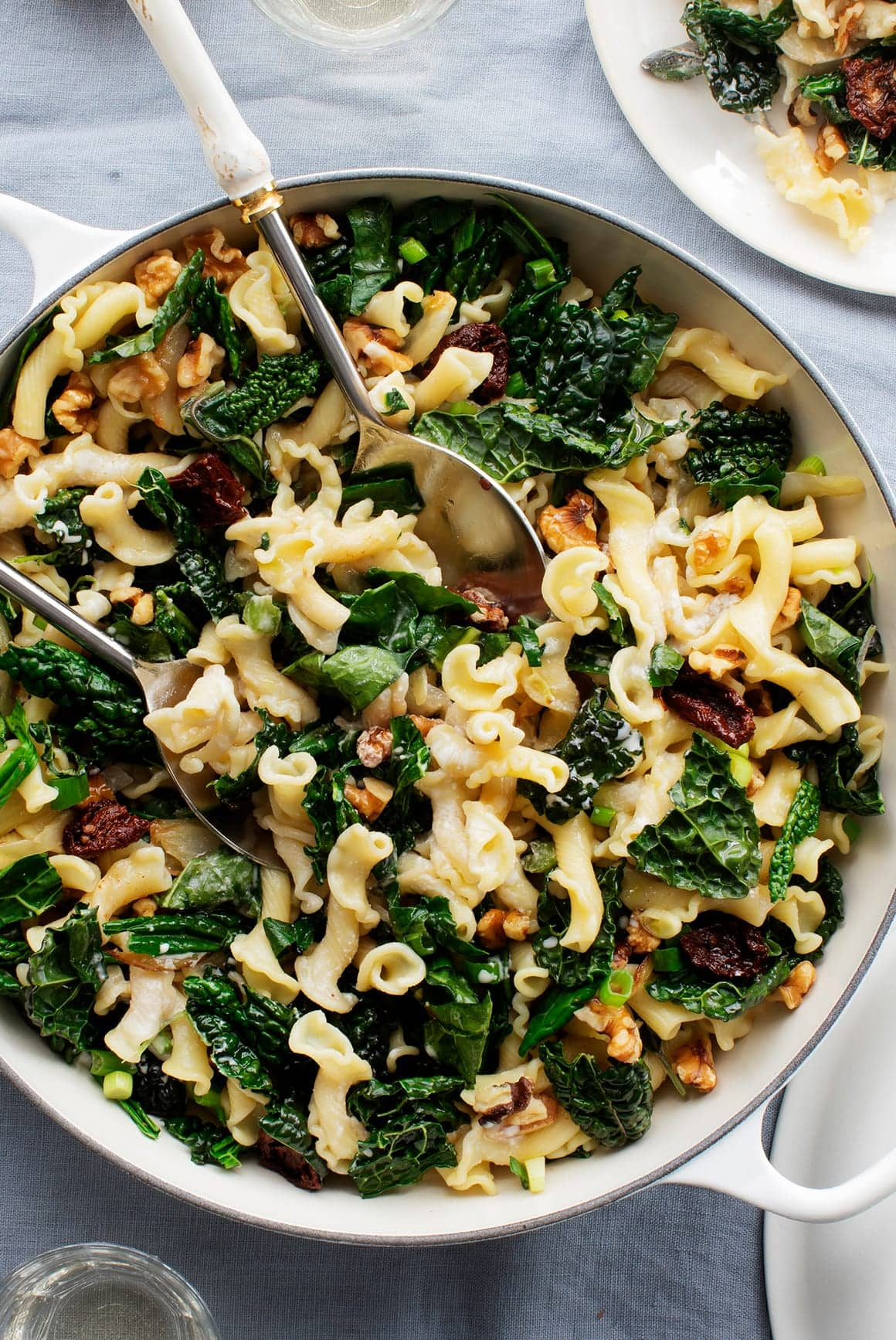 white pot with noodles, kale, and sun-dried tomatoes