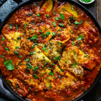 black cast iron pot with zucchini lasagna and red sauce in it on brown board with fresh herbs surrounding it.