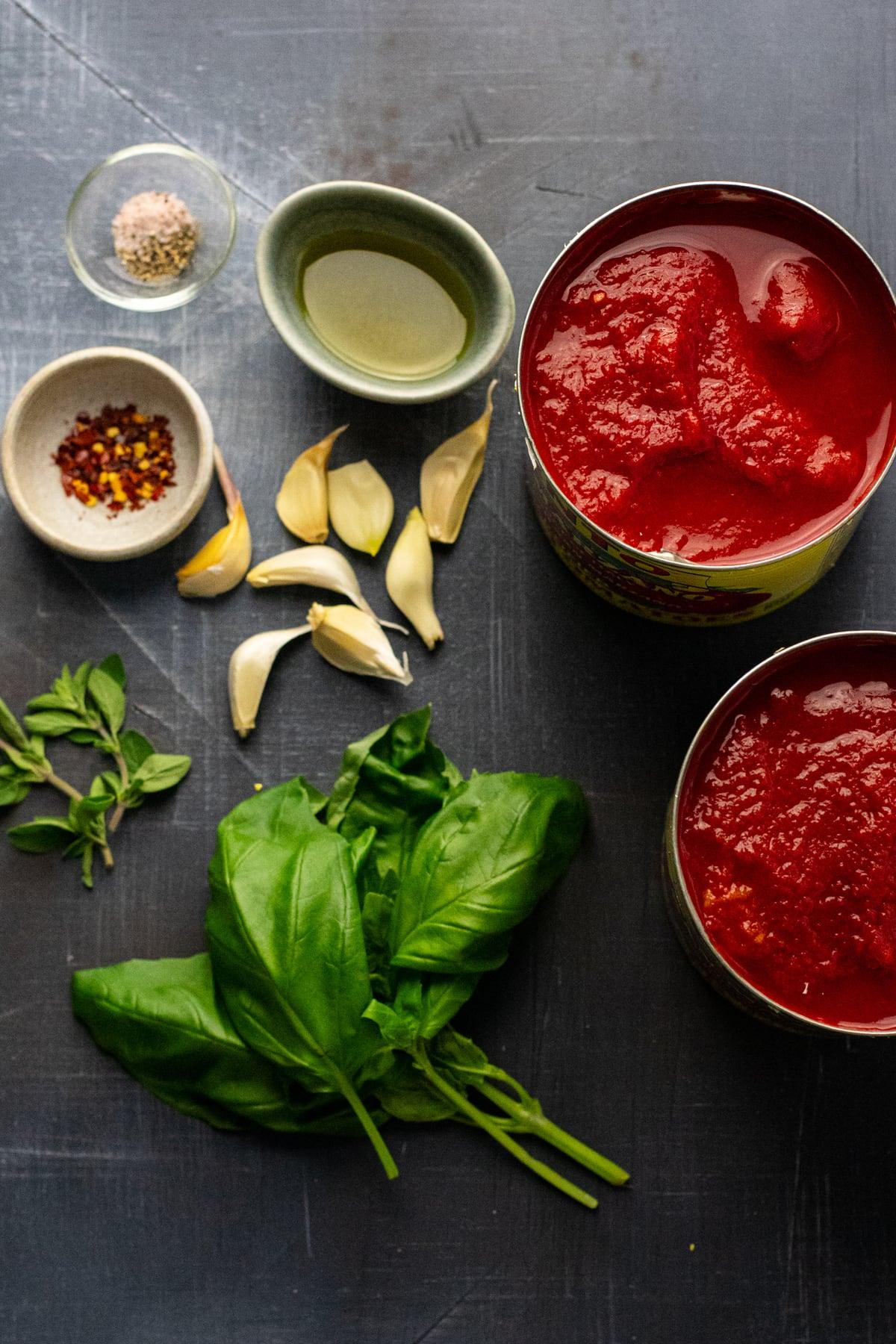 ingredients for arrabbiata tomato sauce arranged on dark gray background.