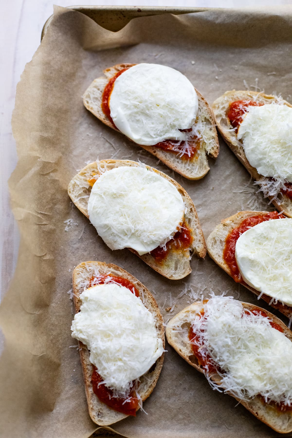 crostini pizzas arranged on pan lined with parchment paper.