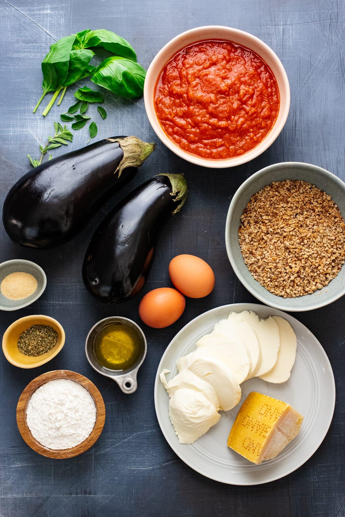 Ingredients for eggplant parmesan arranged on dark gray background.
