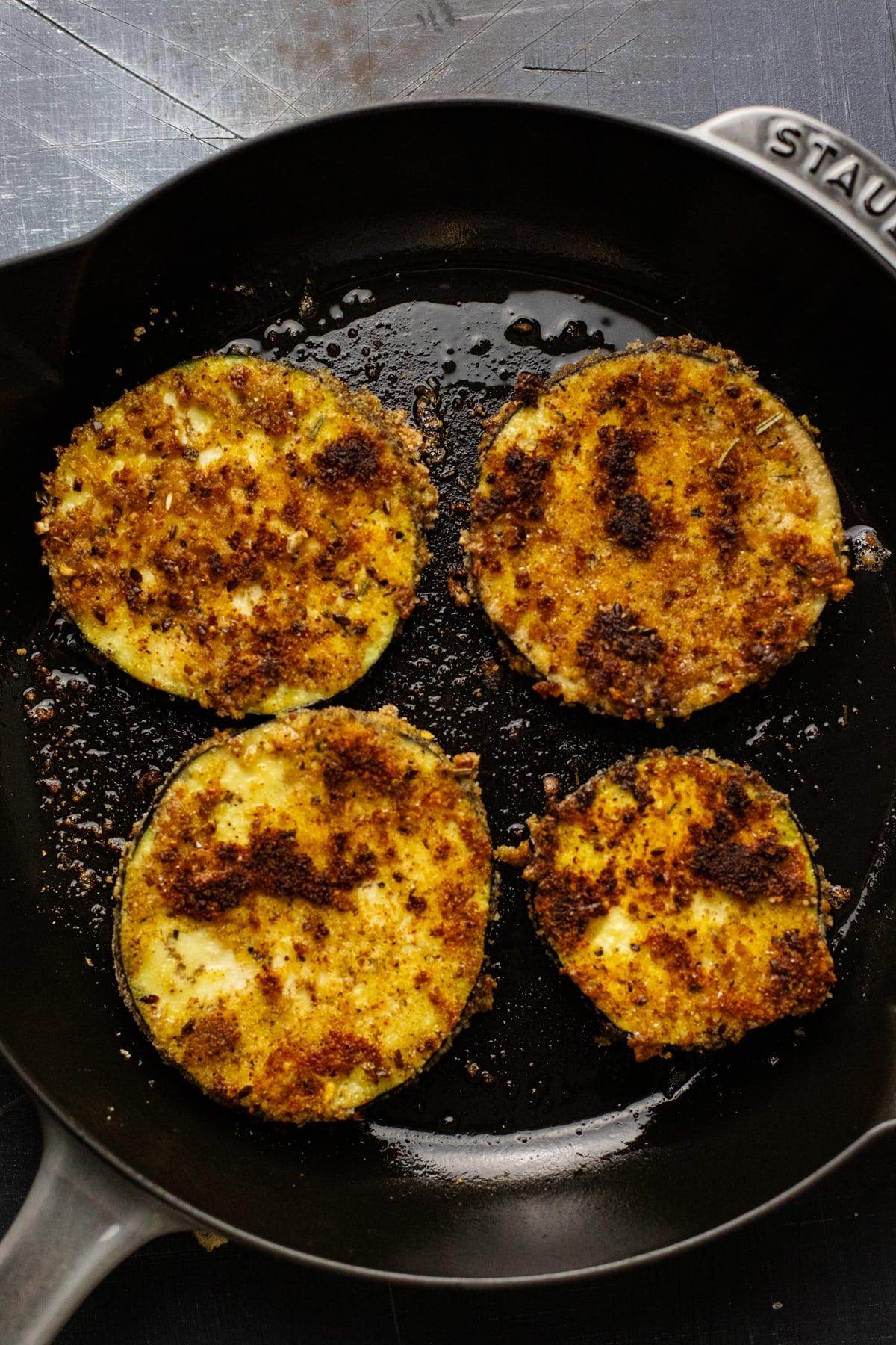breaded eggplant being browned in black skillet pan.
