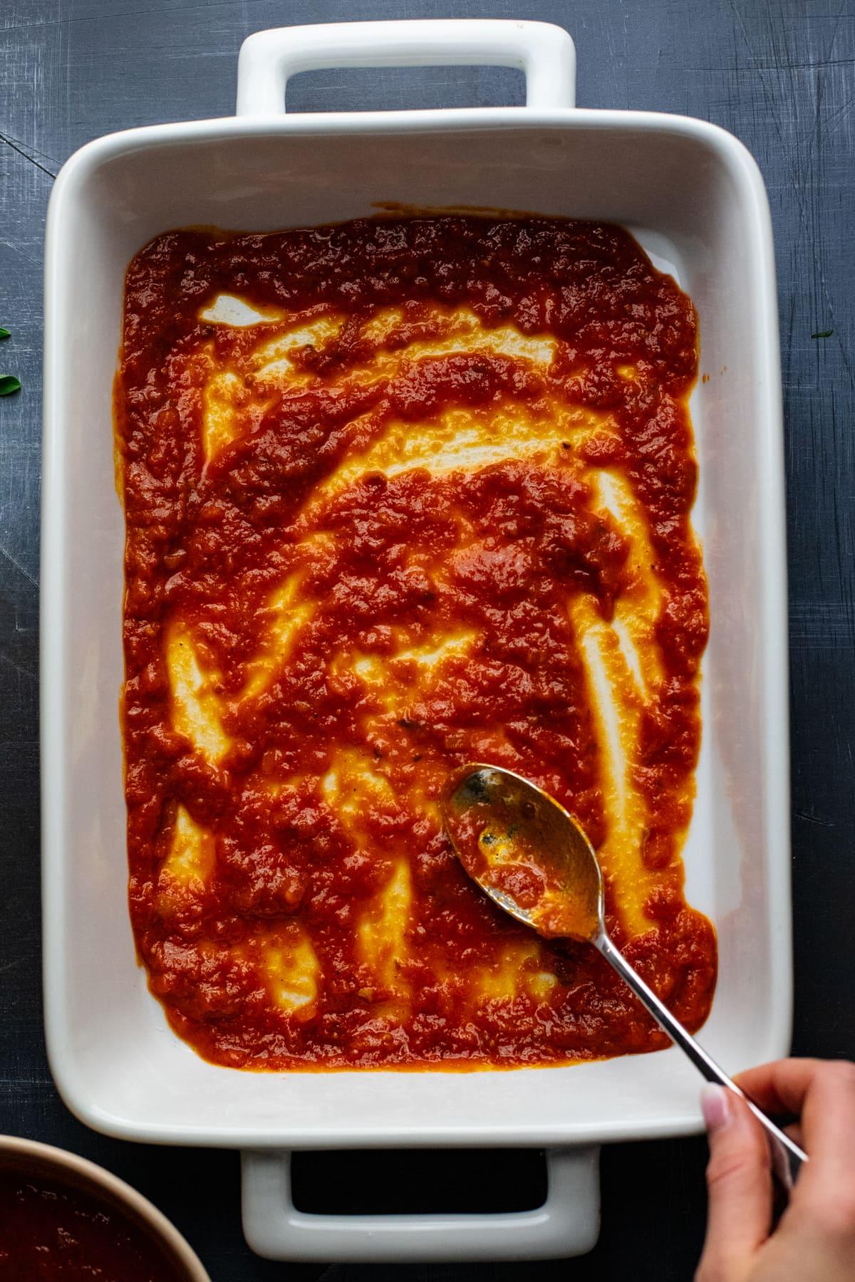 spoon spreading red marinara sauce in white baking dish.