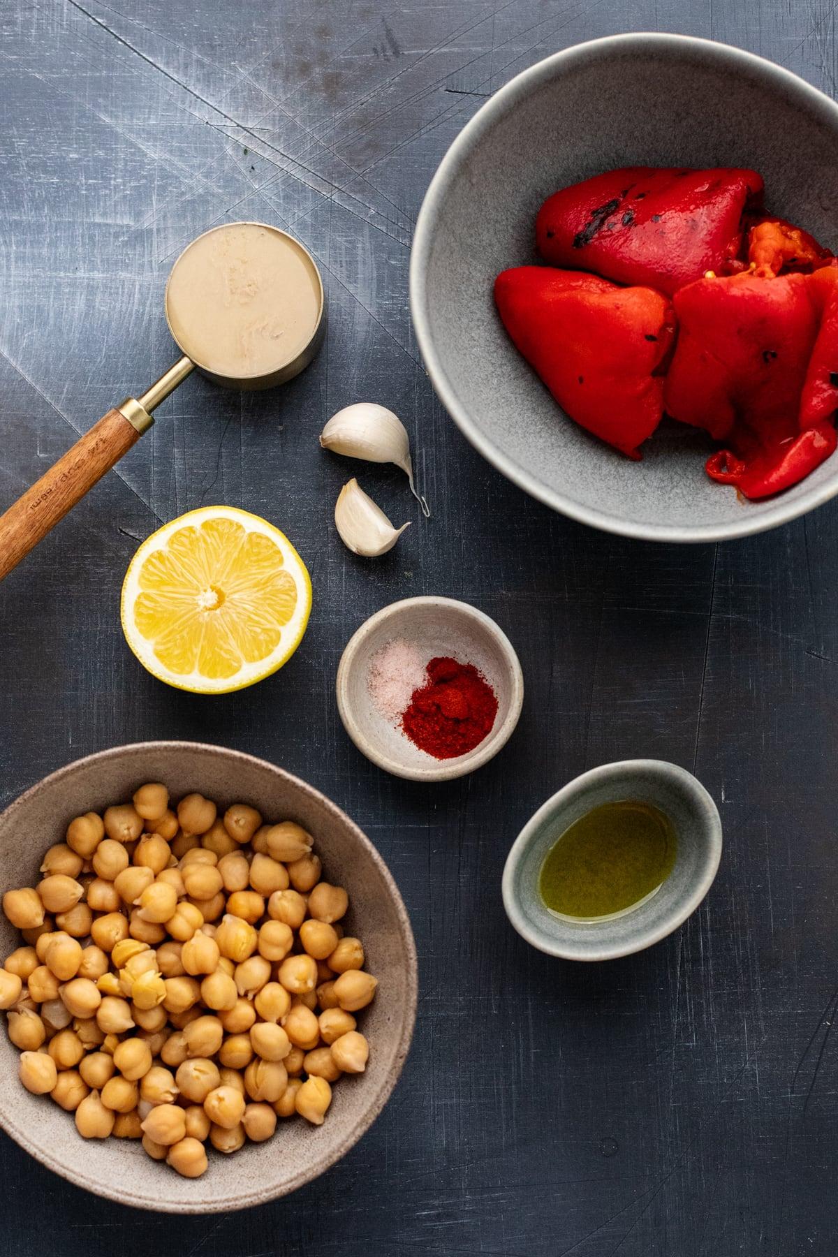 ingredients for red pepper hummus arranged on dark gray background.