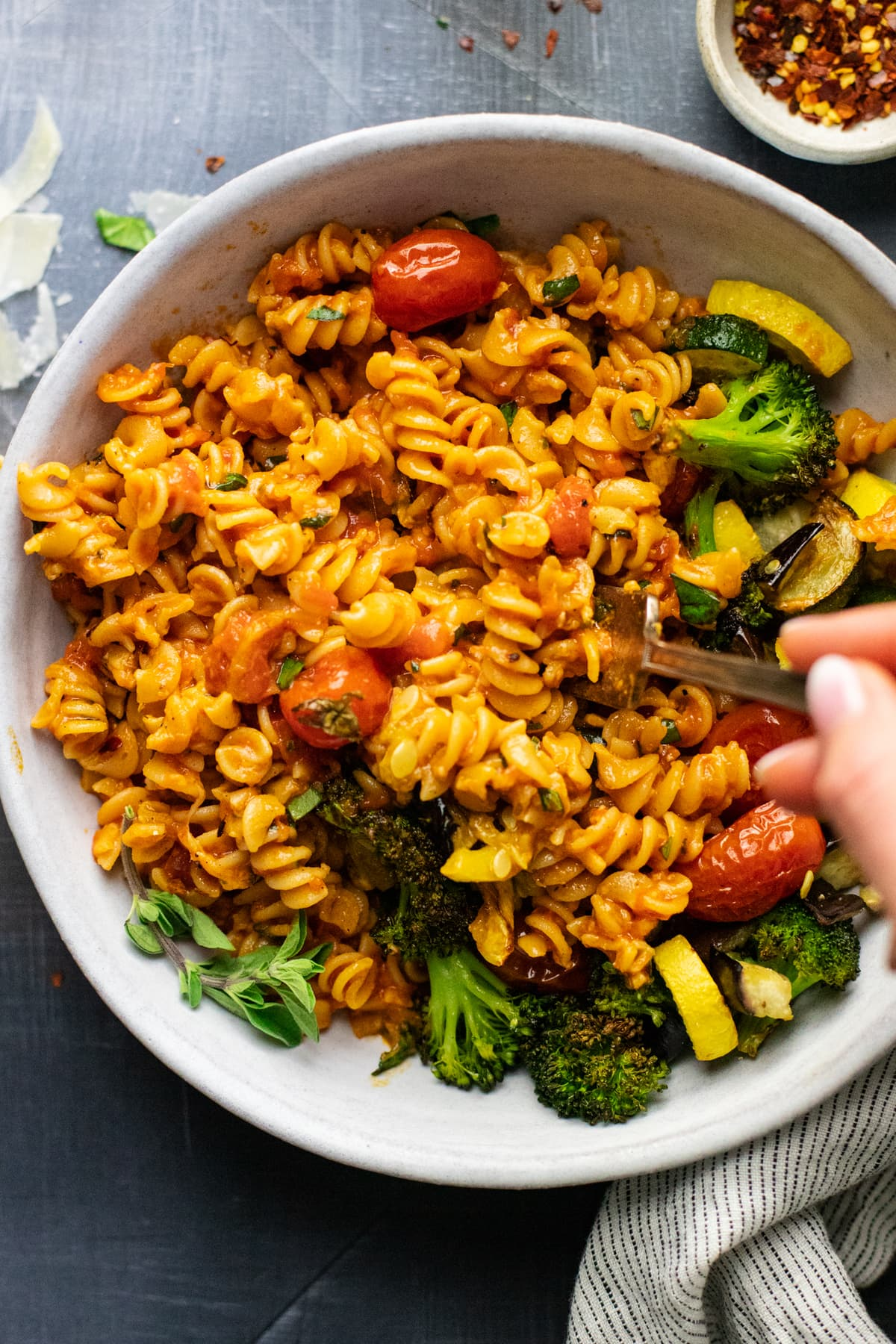 hand holding fork in white bowl of rotini pasta noodles and roasted vegetables.