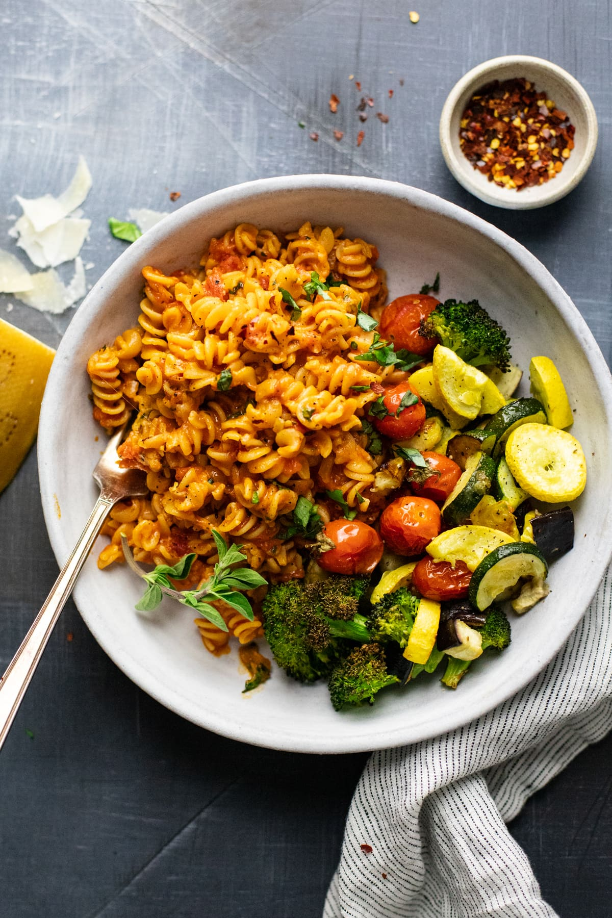 white bowl with rotini pasta noodles and roasted vegetables in it on gray background with shredded cheese and red pepper flakes arranged around it.