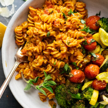 white bowl with rotini pasta and roasted vegetables on gray background.