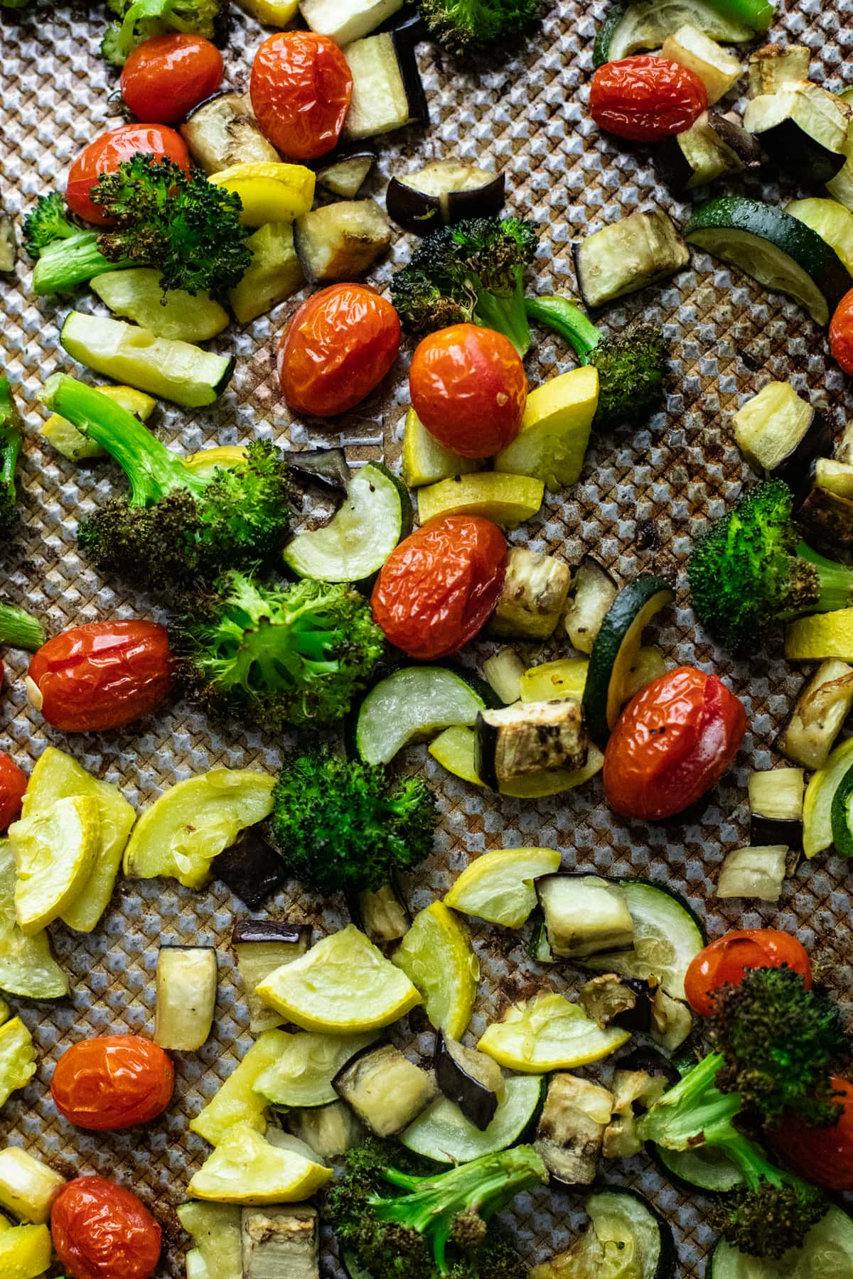 assorted roasted vegetables arranged on sheet pan.
