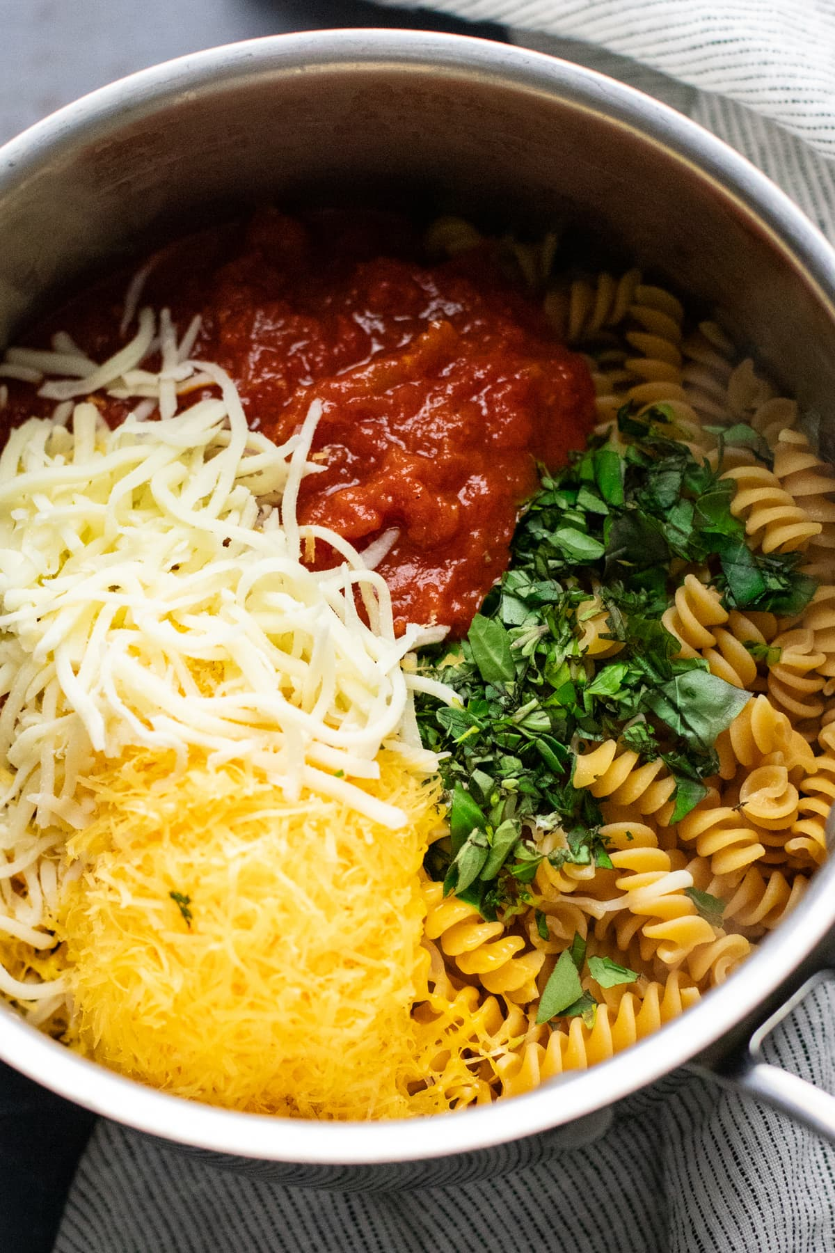 a pot with cheese, red tomato sauce, fresh herbs, and rotini pasta in it.