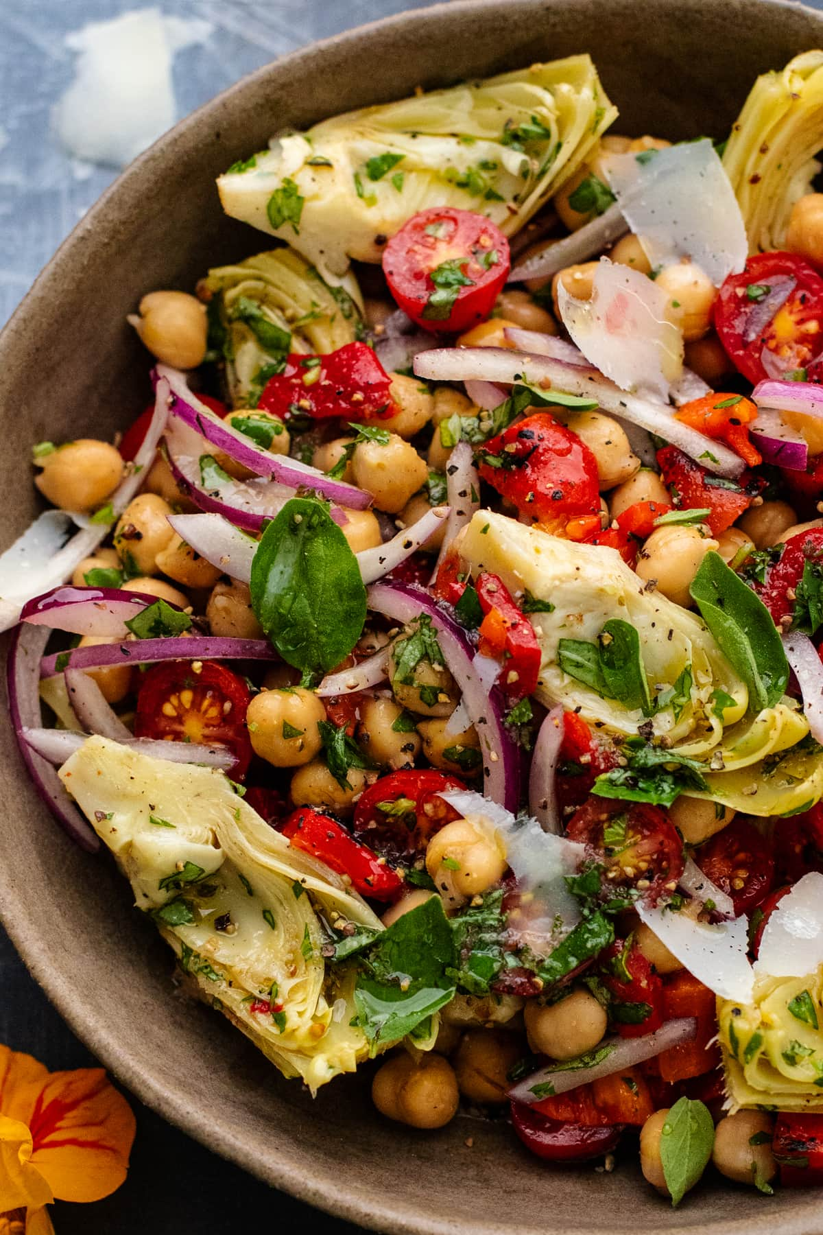close up of artichokes and garbanzo bean salad in a ceramic bowl.
