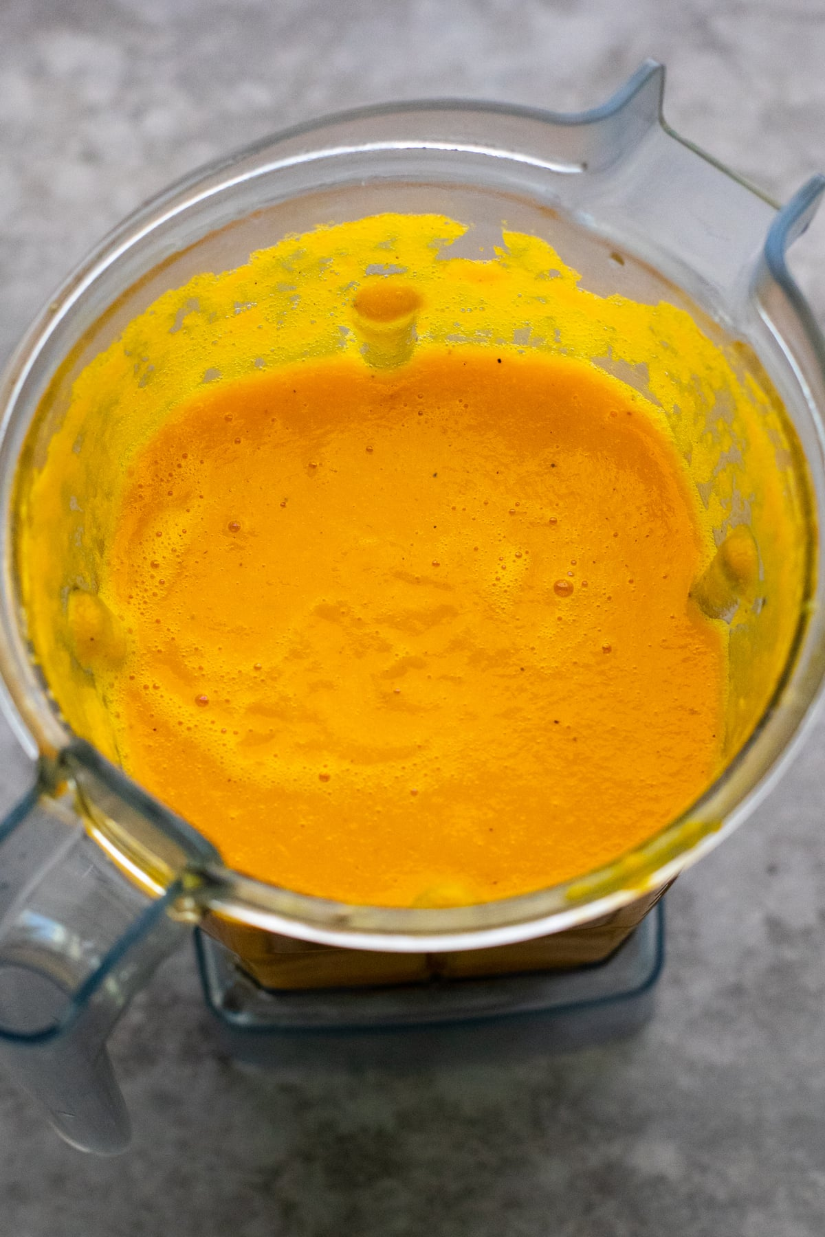 Orange carrot soup pureed in blender container.
