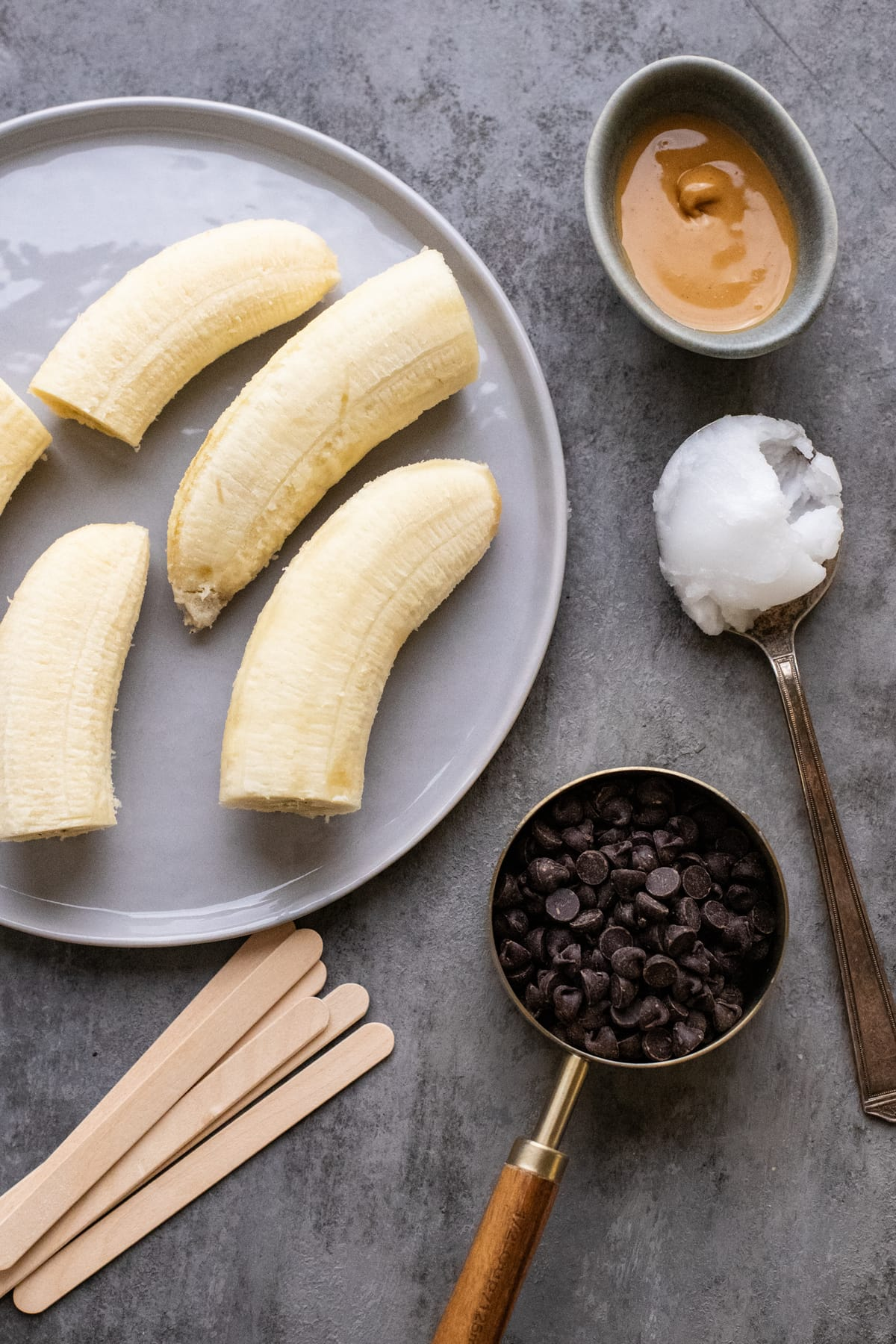 ingredients for frozen chocolate-covered bananas arranged on dark gray background.