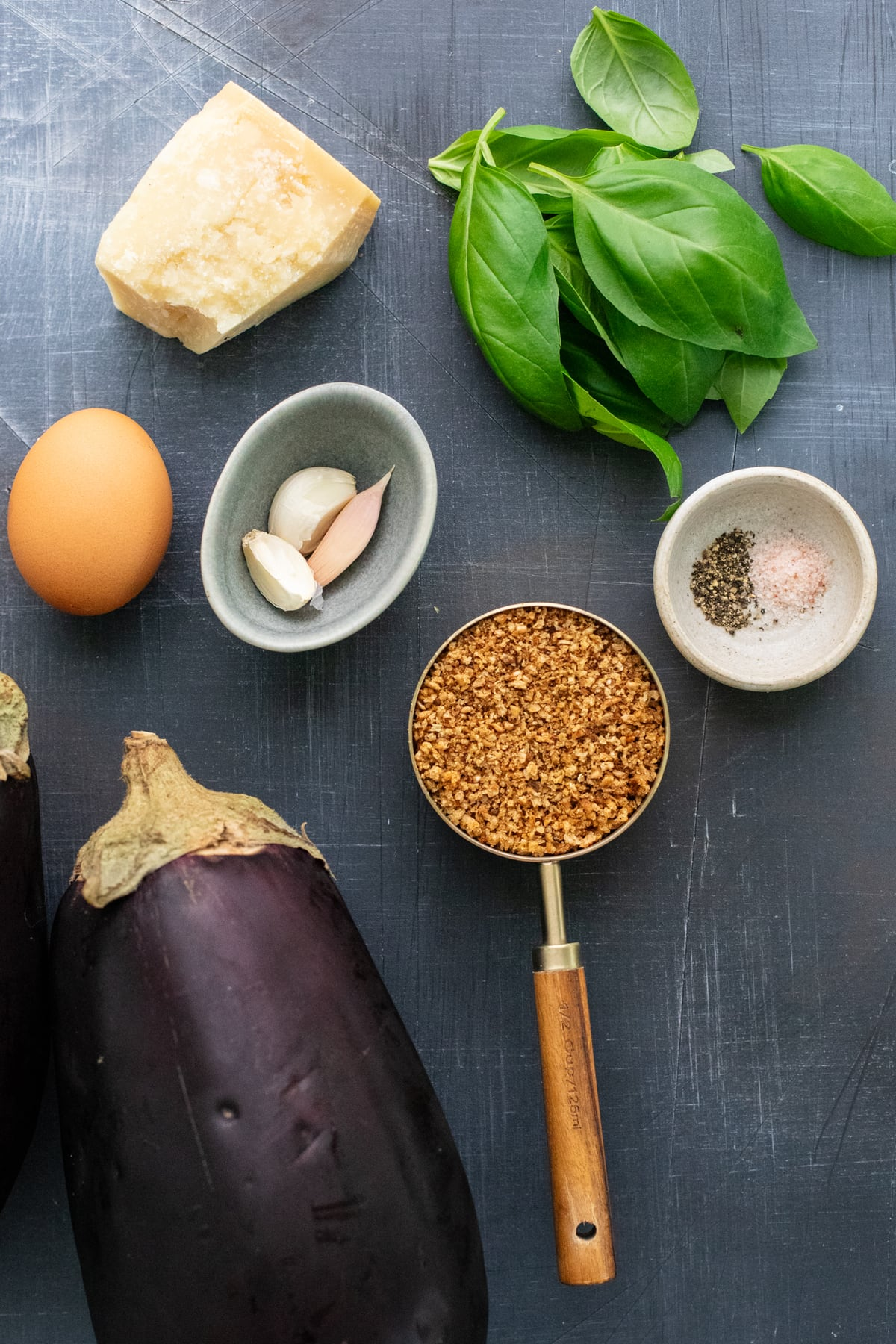 ingredients for eggplant meatballs arranged on a dark gray background.