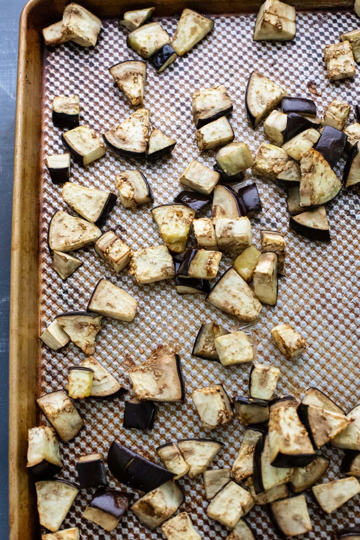 roasted eggplant pieces arranged on baking sheet.