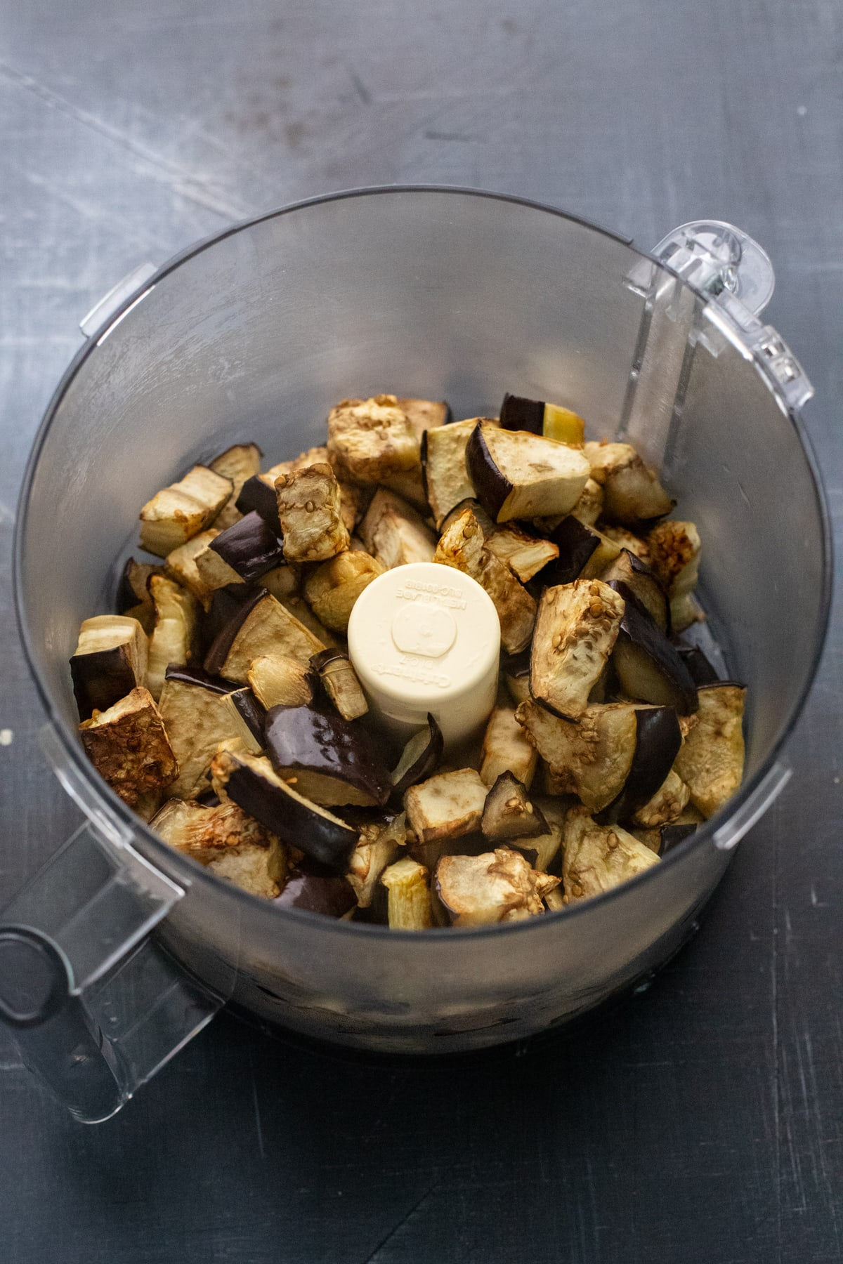 Food processor with eggplant pieces in it.