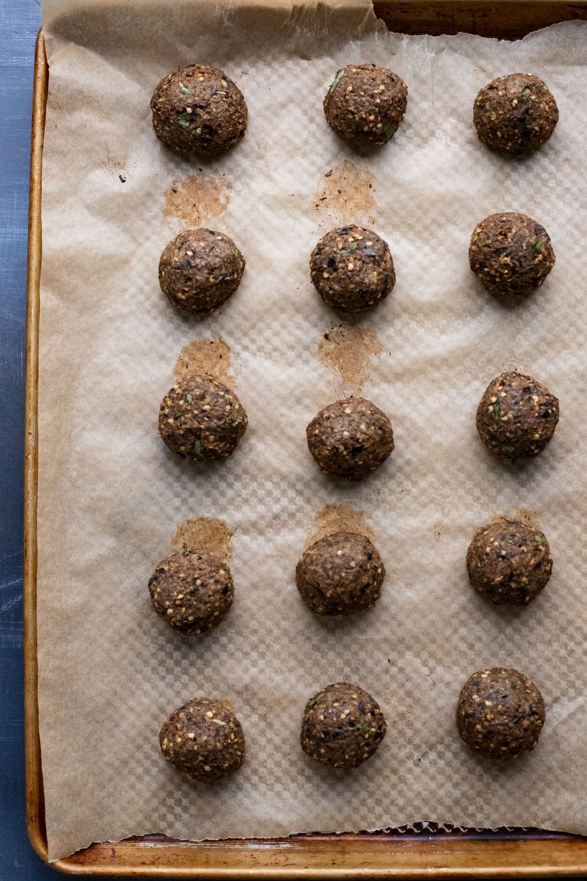 Cooked eggplant meatballs on a baking sheet lined with parchment paper.