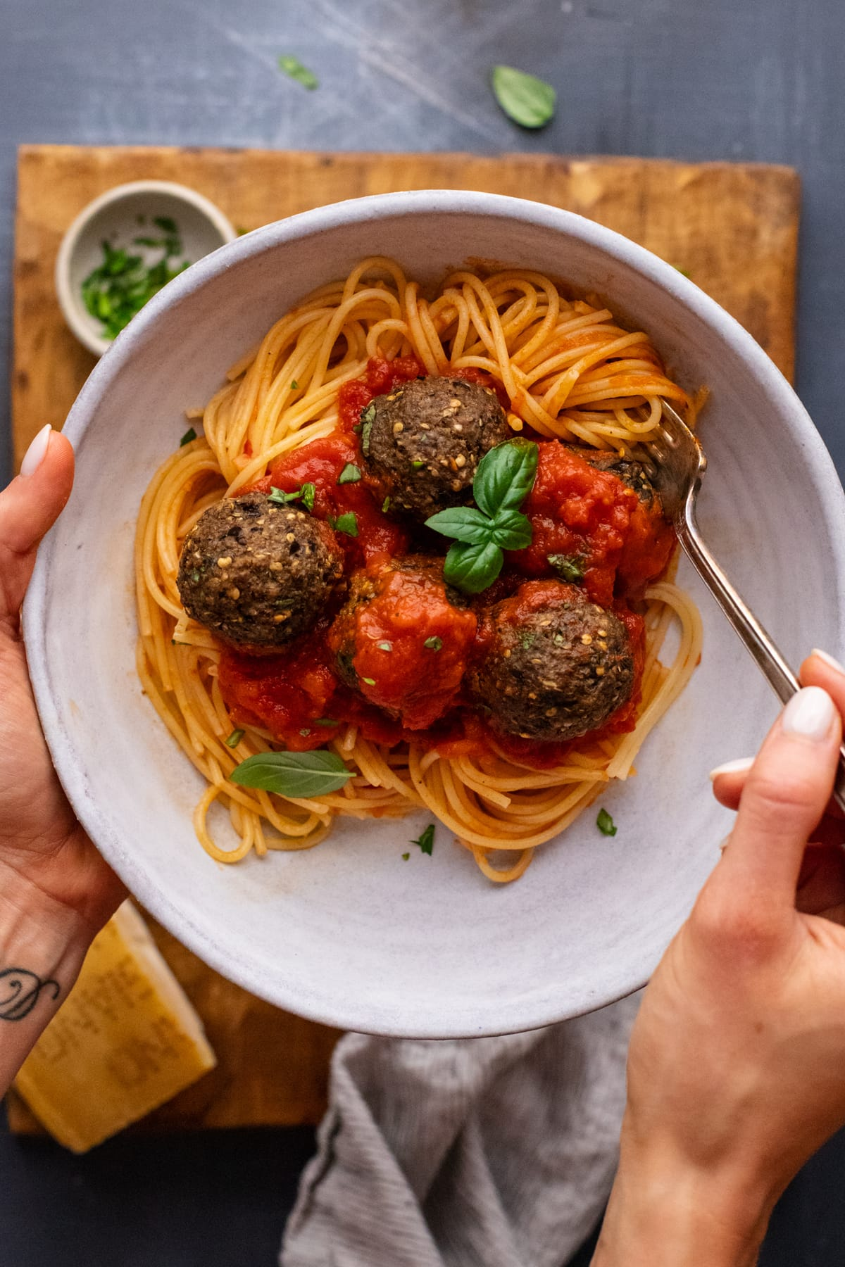 hand holding white bowl with spaghetti and eggplant meatballs with red tomato sauce in it over a brown wooden board.