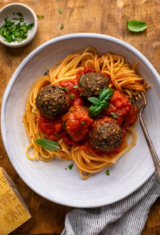 white bowl with spaghetti and eggplant meatballs with red sauce in it on brown wooden board.