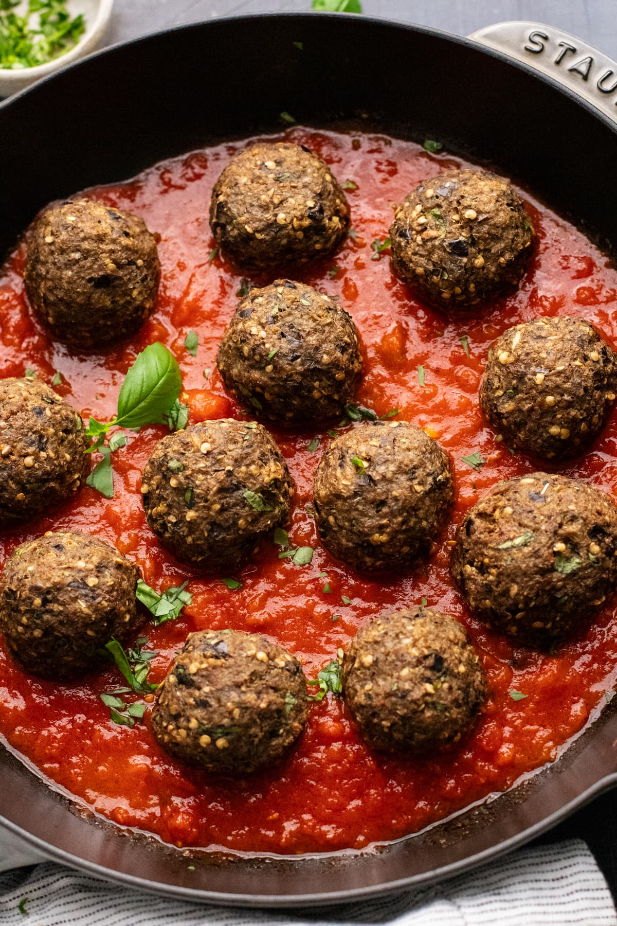 a black skillet with eggplant meatballs and red tomato sauce in it.