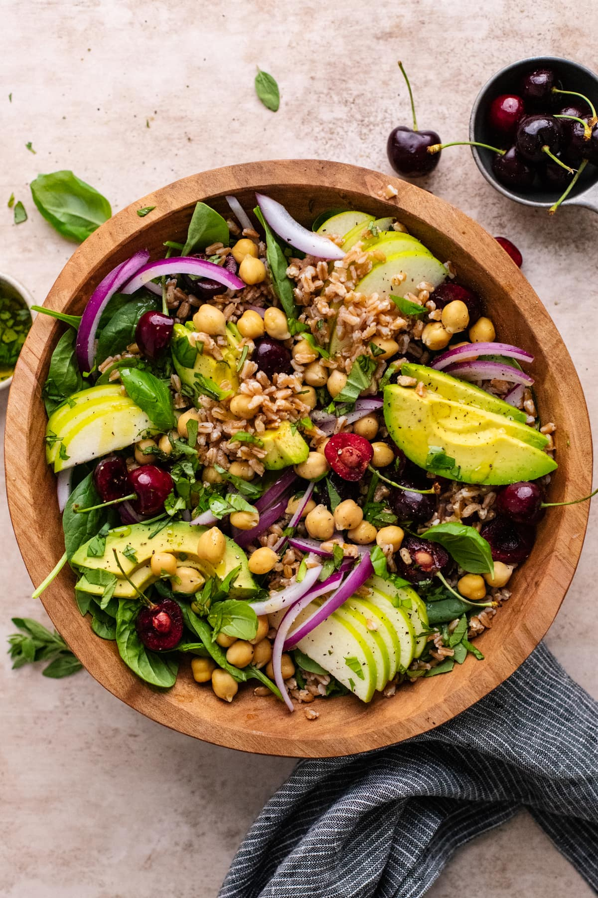 wooden bowl filled with farro salad topped with sliced avocados and cherries.