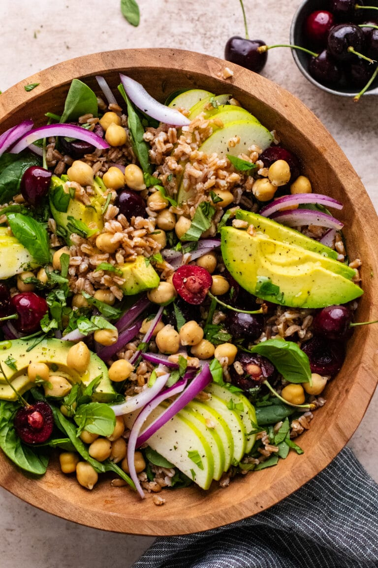 Farro salad with sliced avocado and cherries in a brown wooden bowl.
