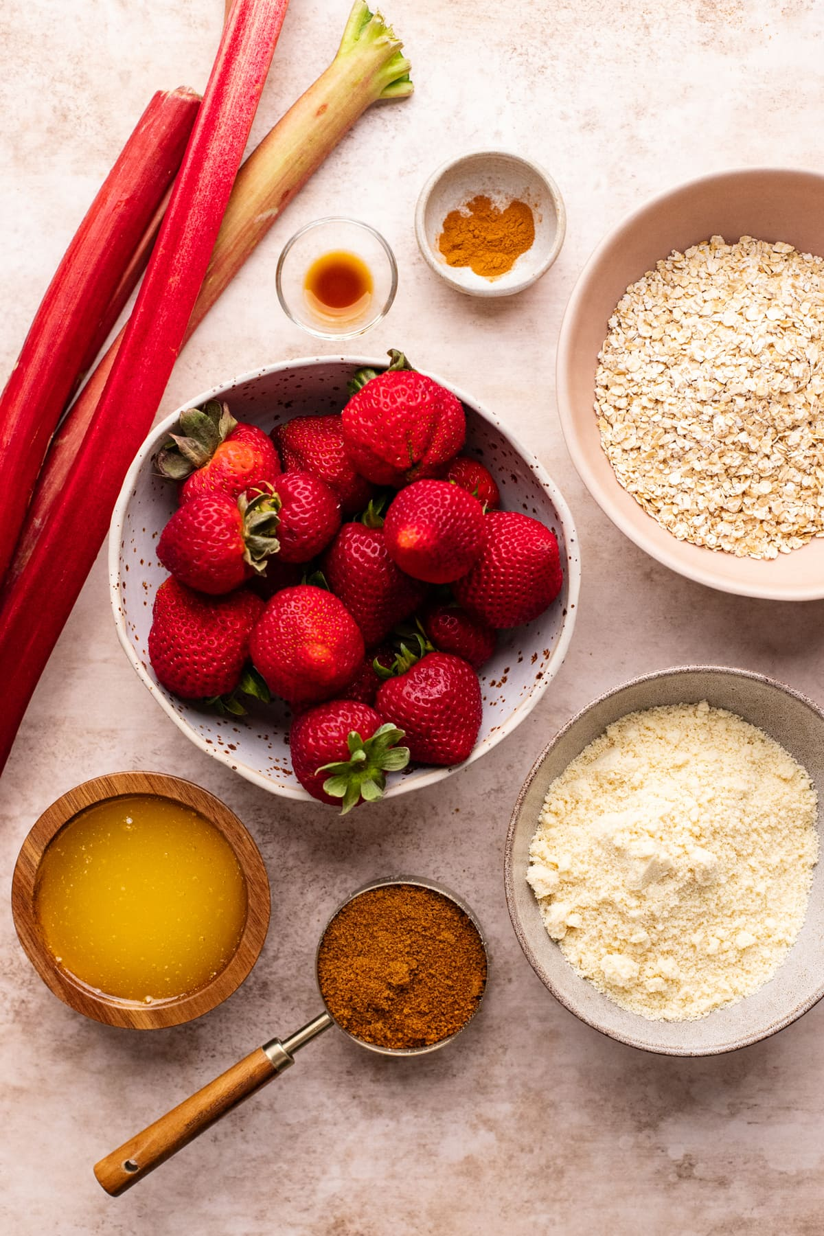 ingredients for gluten free strawberry rhubarb crisp arranged on a tan colored background.