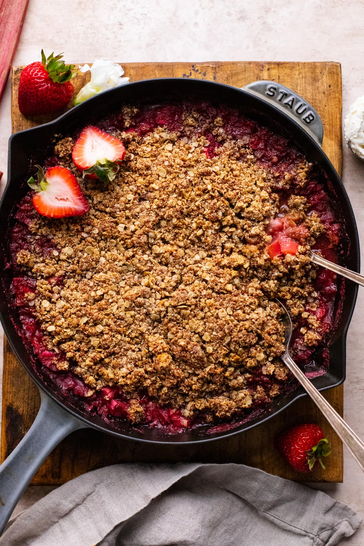 skillet pan with gluten free strawberry rhubarb crisp in it on brown wooden board.