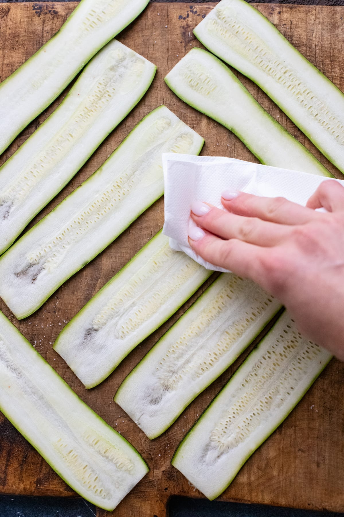 hand using napkin to dry zucchini noodles on wooden board.