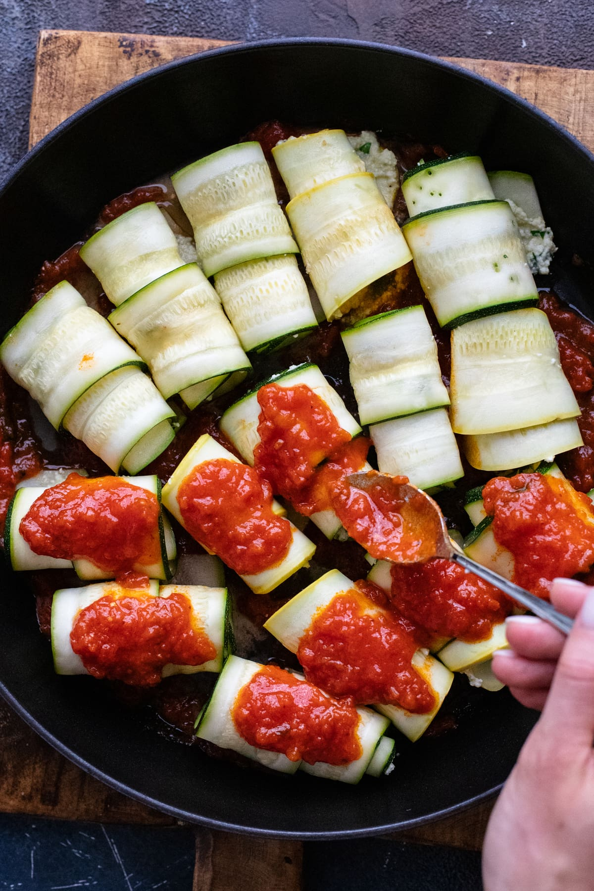hand spooning red sauce over zucchini rollatini in black skillet.