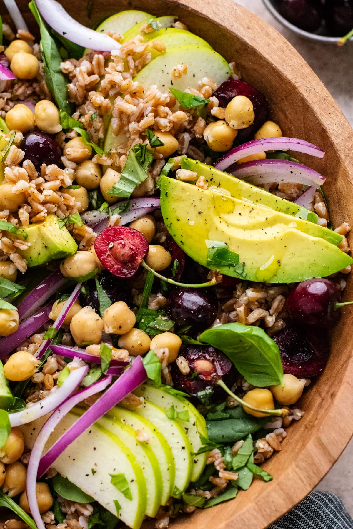 farro salad in a wooden bowl with avocado slices and cherries.