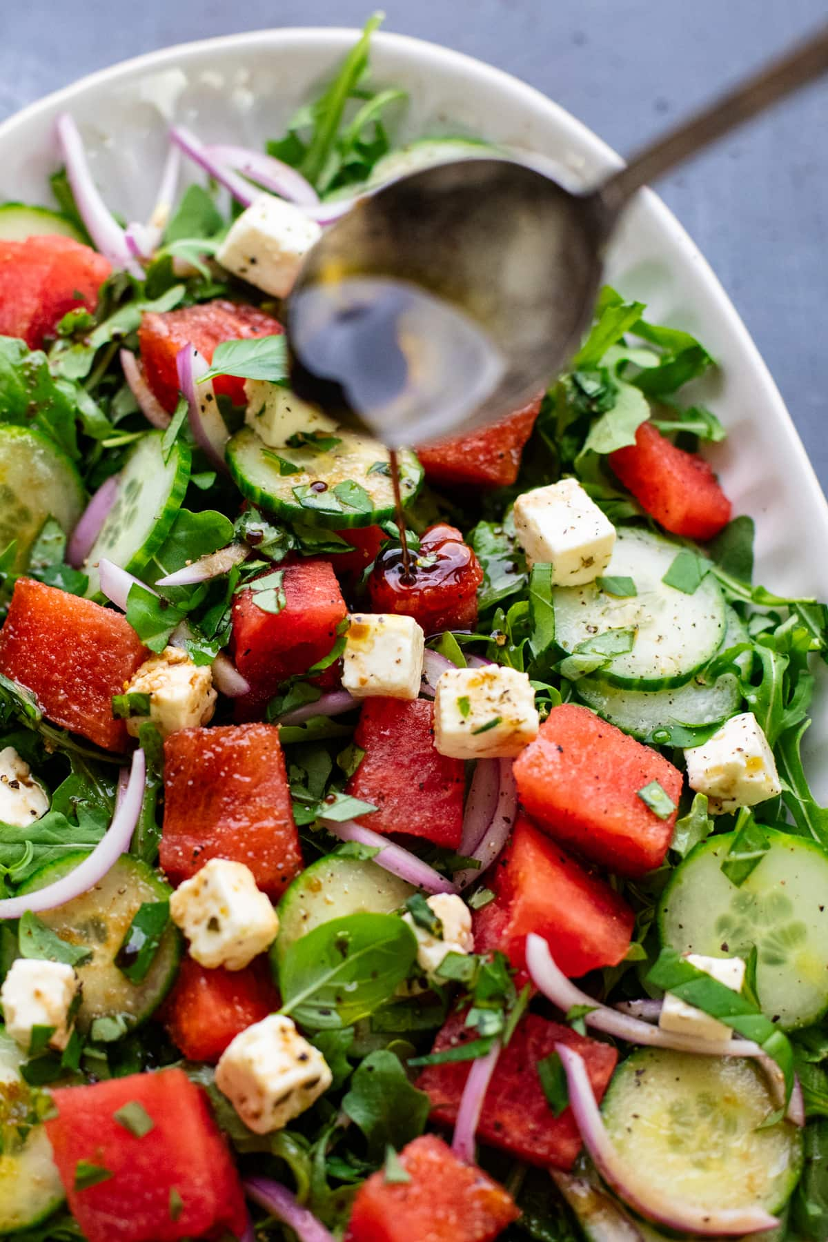 spoon drizzling dressing over watermelon salad.