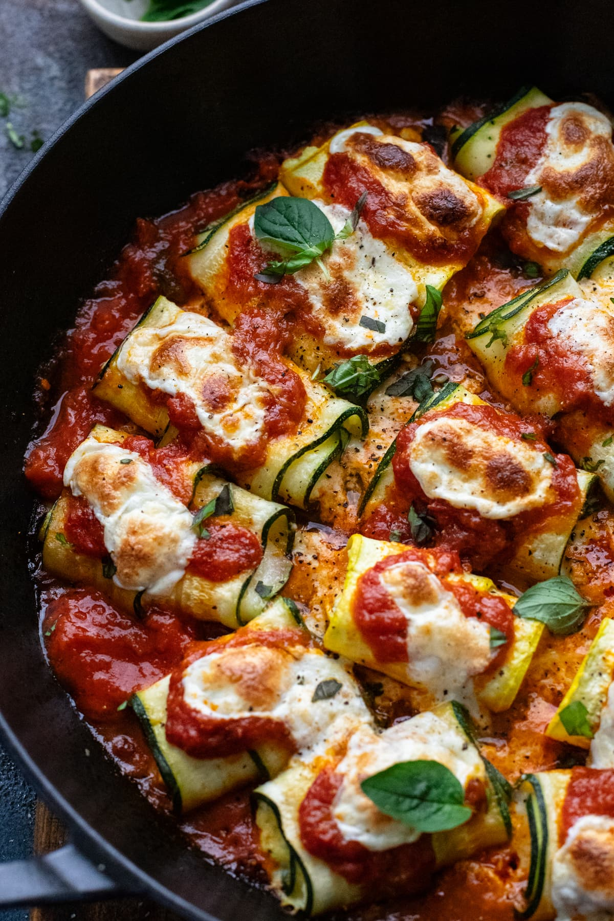 zucchini rollatini baked in a cast iron pan with red sauce and melted cheese.