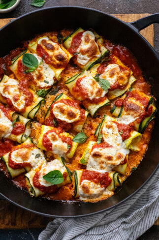 black cast iron skillet with red sauce and zucchini rollatini in it.