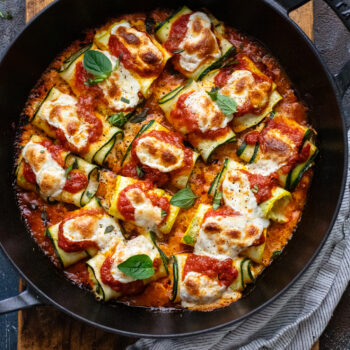 black cast iron pan with zucchini rollatini with red sauce in it on a brown wooden board and dark background.