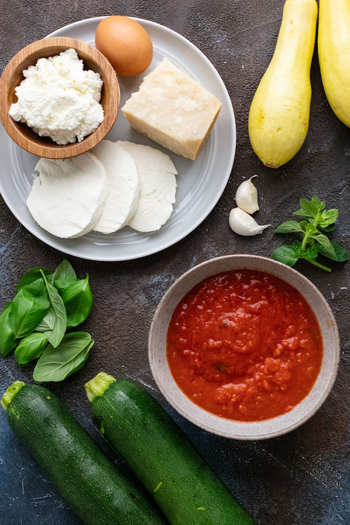 ingredients for zucchini rollatini arranged on a dark gray background.