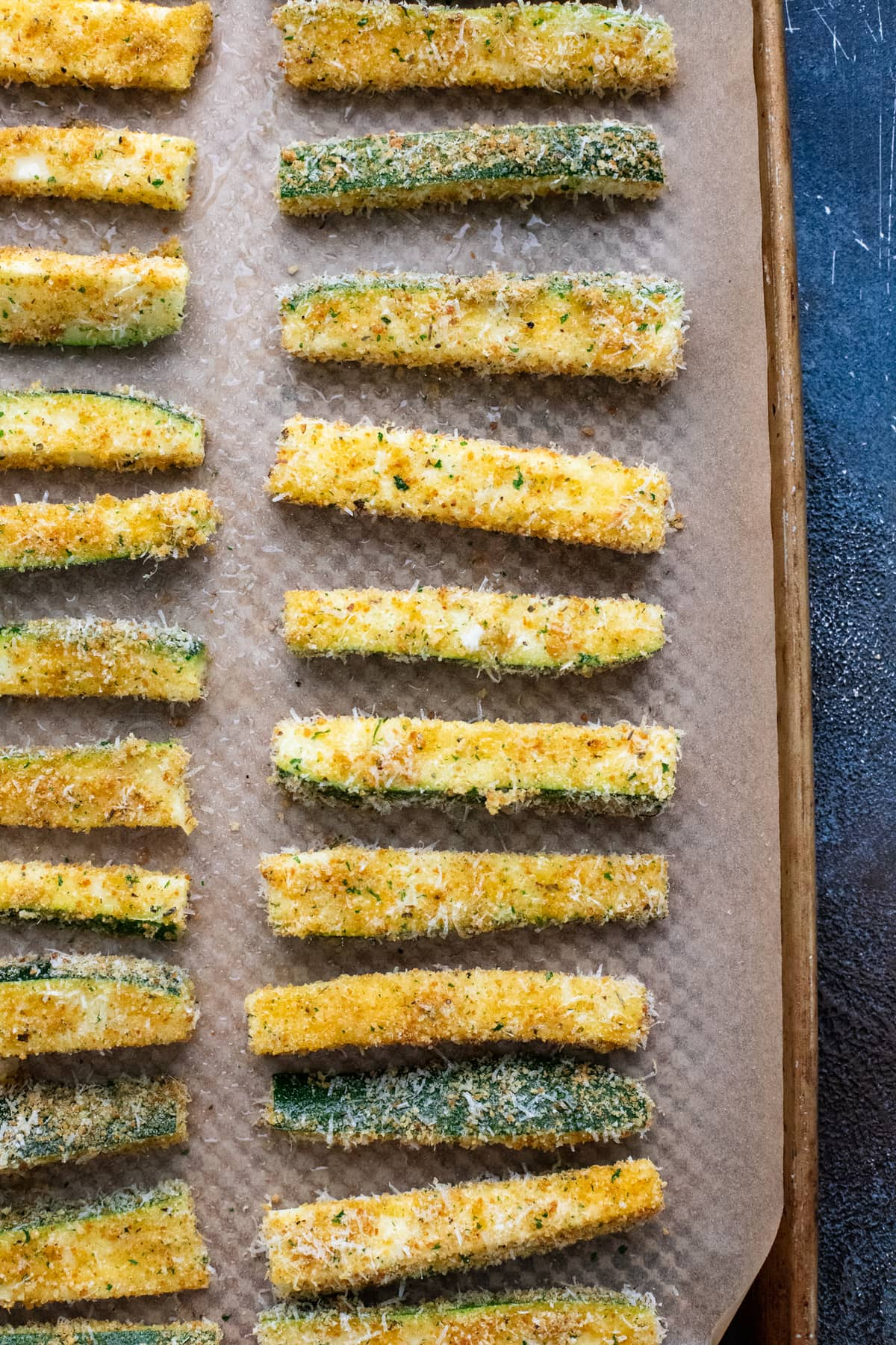 zucchini fries arranged on baking sheet lined with parchment paper.