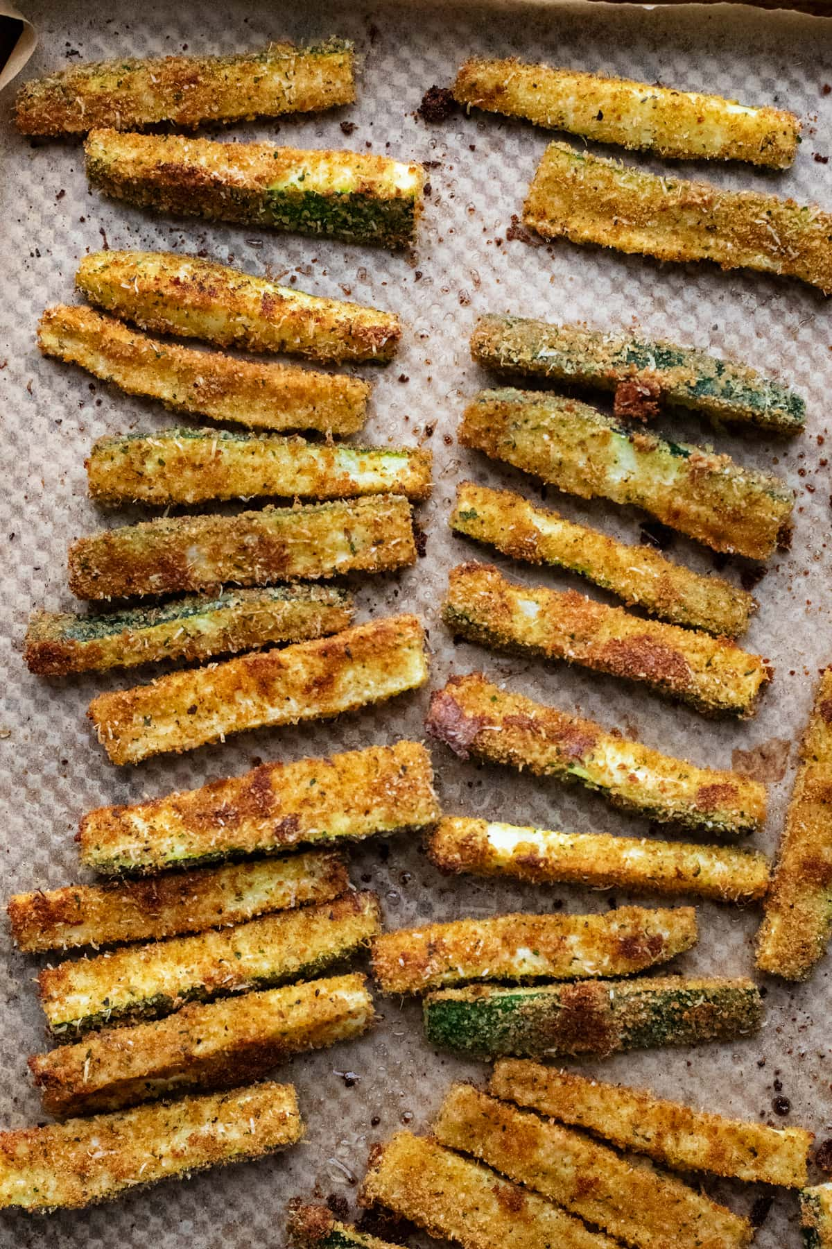 zucchini fries arranged on a sheet pan.