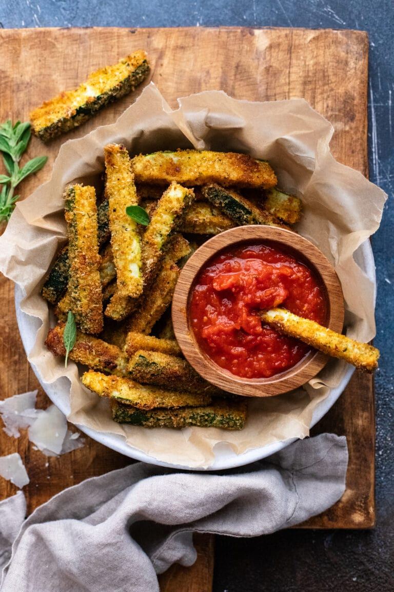a bowl lined with parchment paper with zucchini fries in it with a wooden bowl of red tomato sauce on brown wooden board.