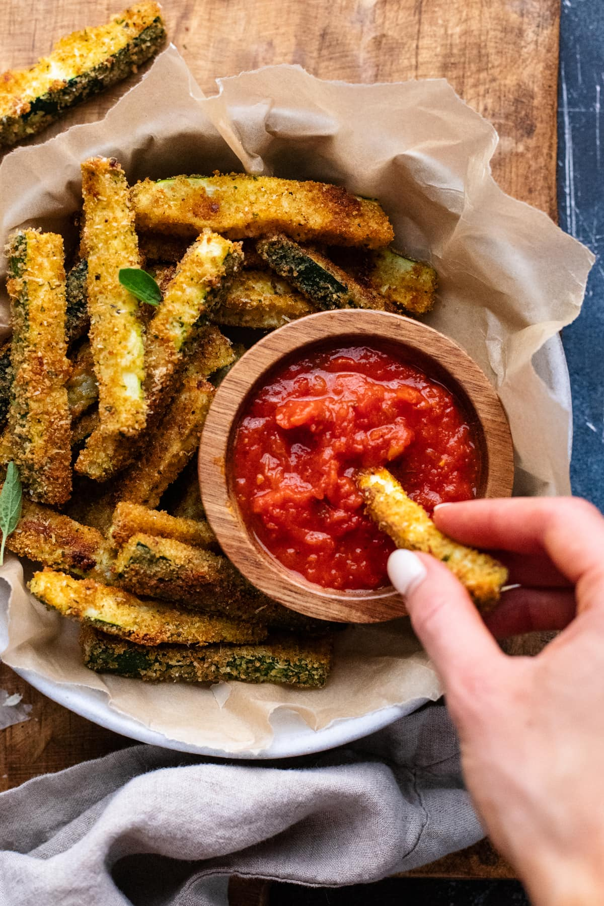 hand dipping zucchini fry into small dish with red tomato sauce in it in larger bowl filled with zucchini fries in it.