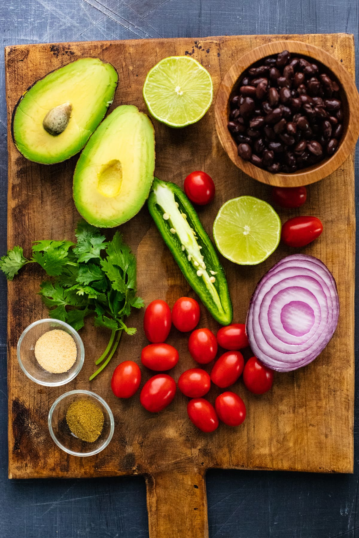 Ingredients for black bean salsa arranged on a brown wooden cutting board.