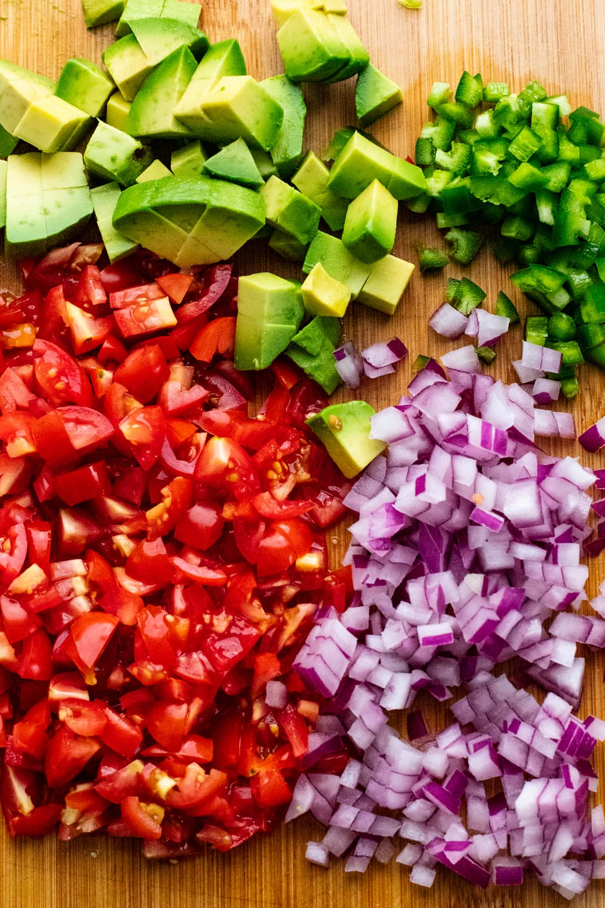 chopped vegetables for salsa arranged on wooden cutting board.