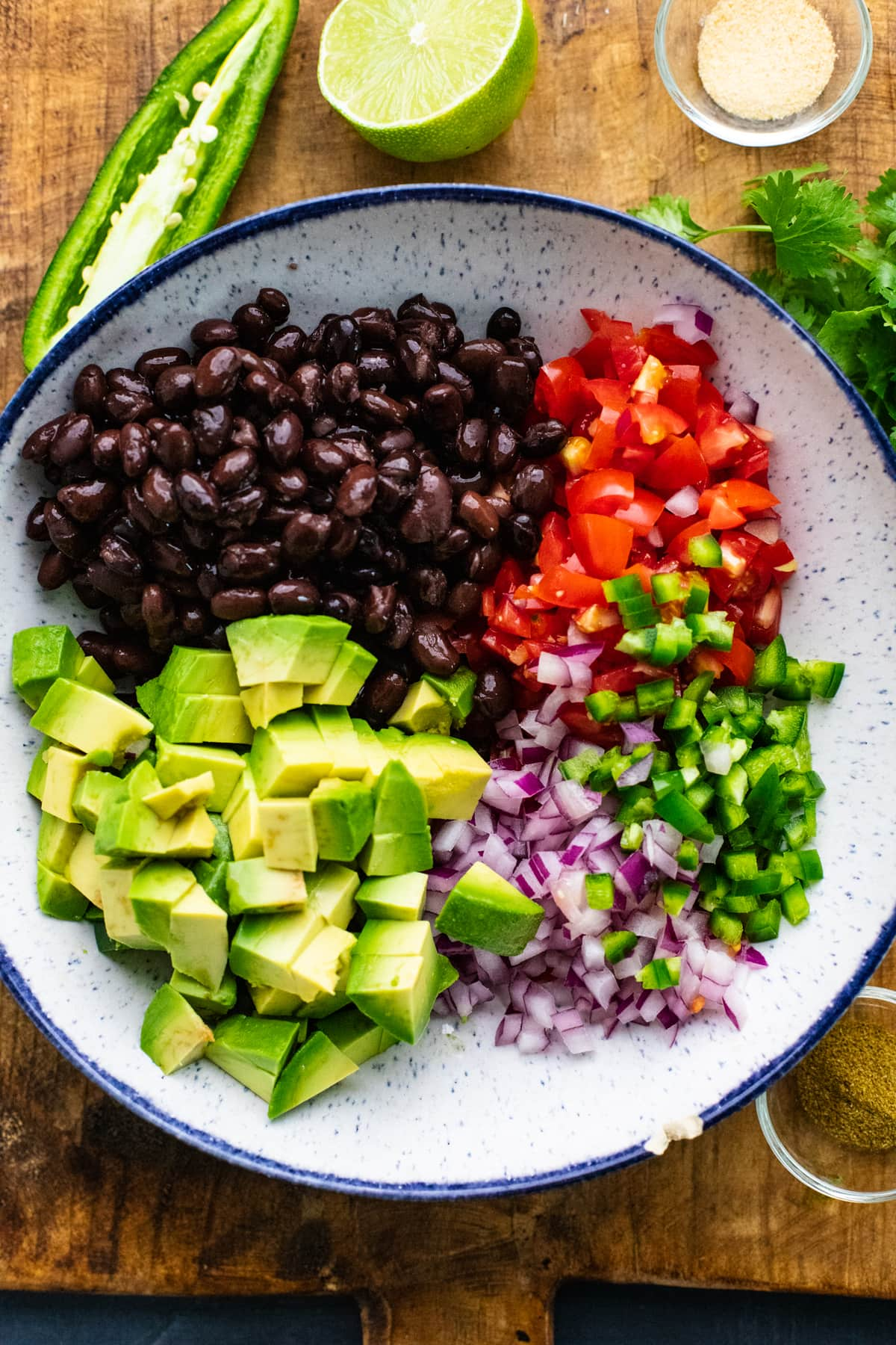 Bowl with black bean salsa ingredients in it on wooden cutting board.