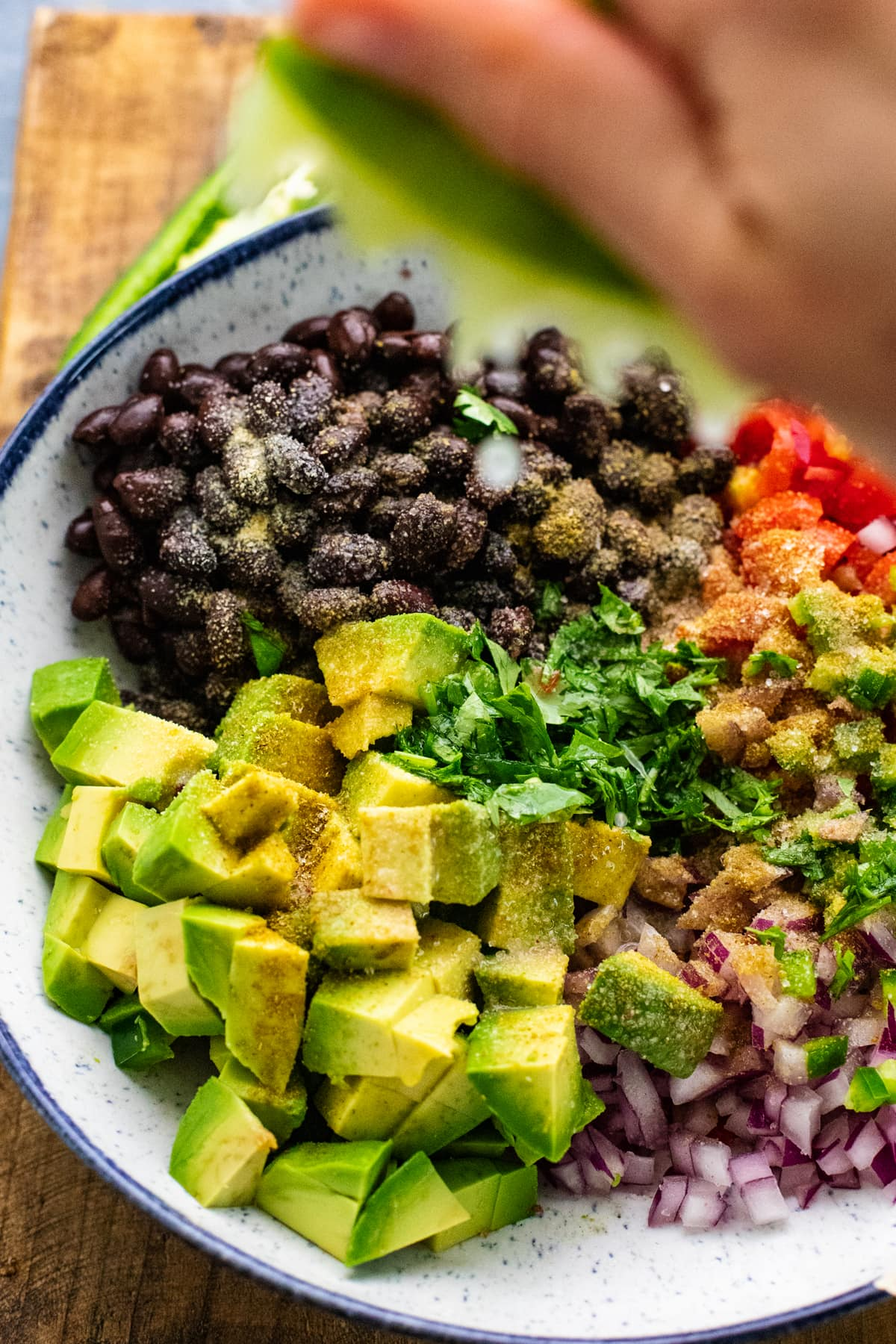 hand squeezing lime over bowl with black bean salsa ingredients in it.