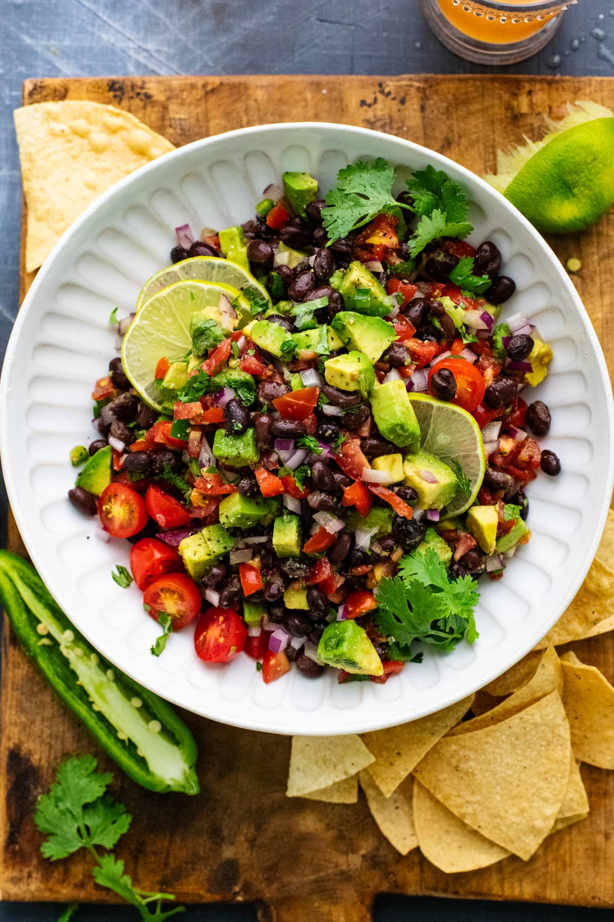 white bowl with black bean salsa in it on wooden board with tortilla chips and lime pieces arranged around it.