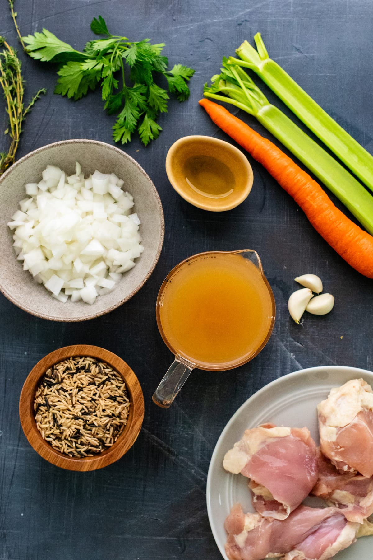 Ingredients for chicken and rice soup arranged on dark gray background.