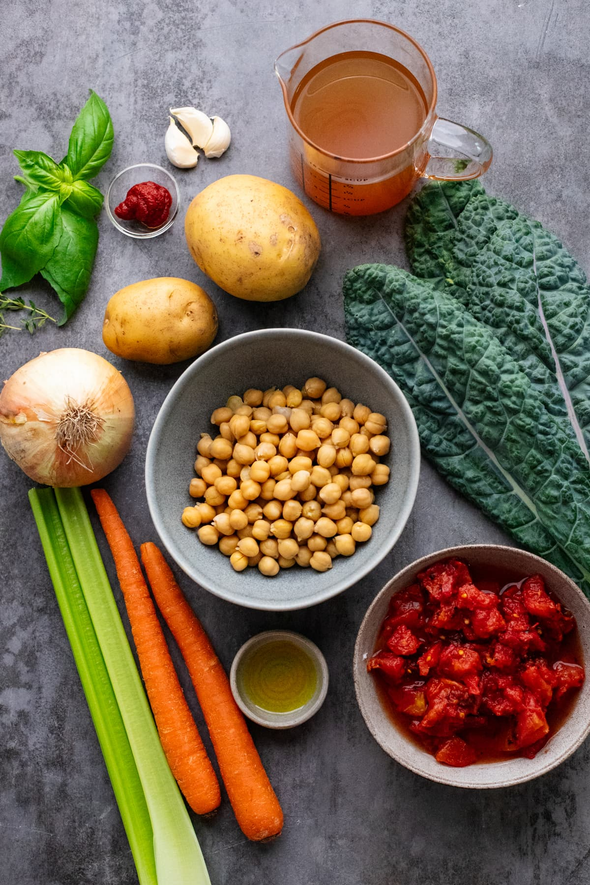 ingredients for chickpea soup arranged on gray background.