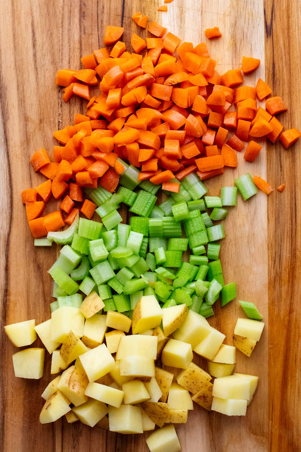 diced vegetables arranged on wooden cutting board.